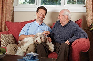 Younger man and senior petting a dog