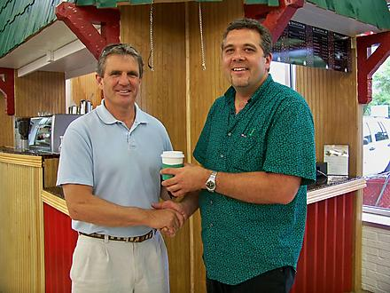 Two Men Shaking Hands and Holding Coffee Cups