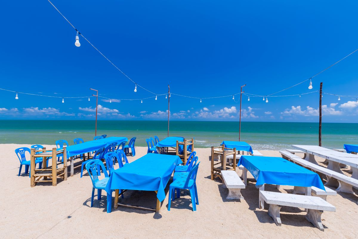 Collection of tables on beach with blue tablecloths