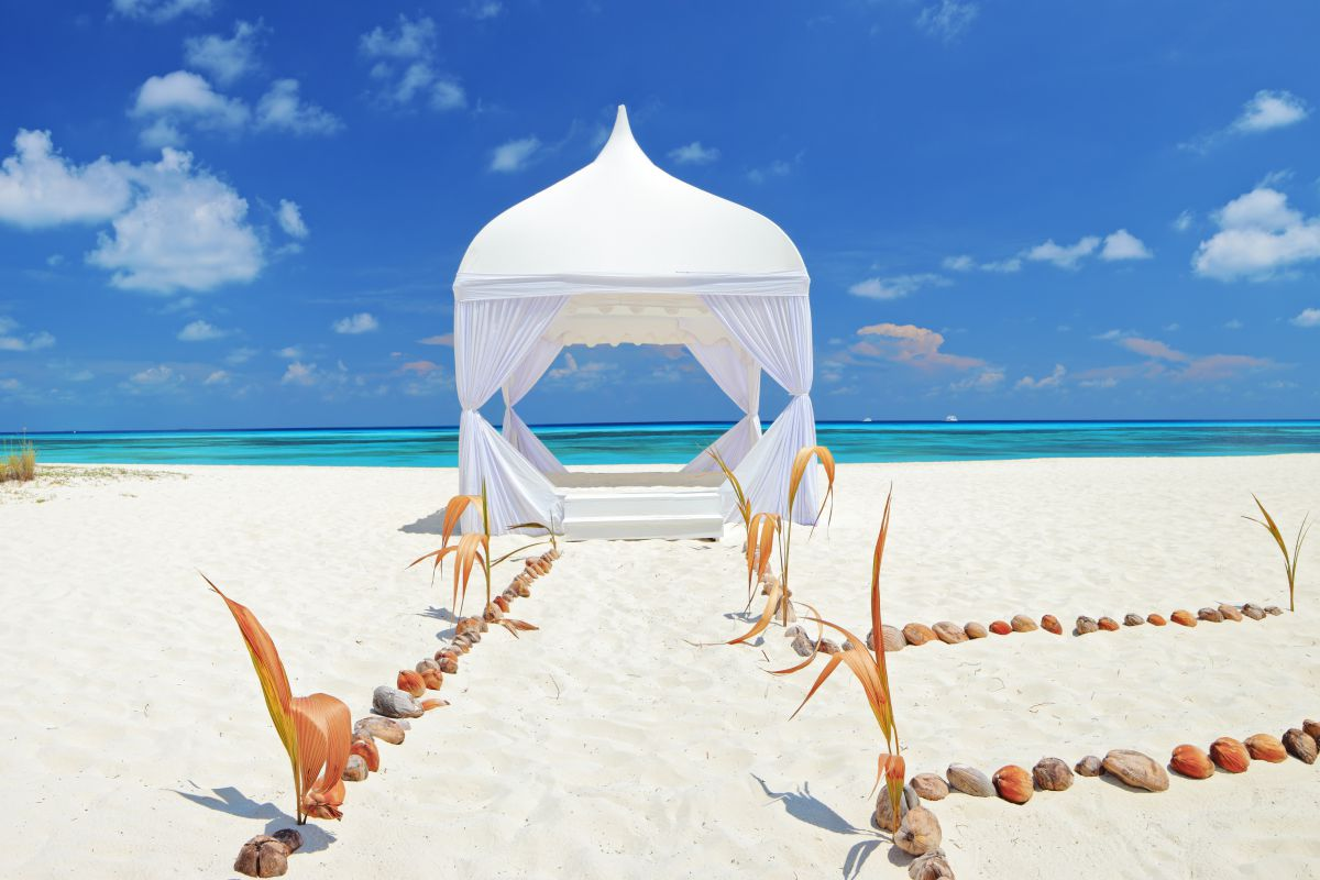 White event tent on beach with stone-lined pathways