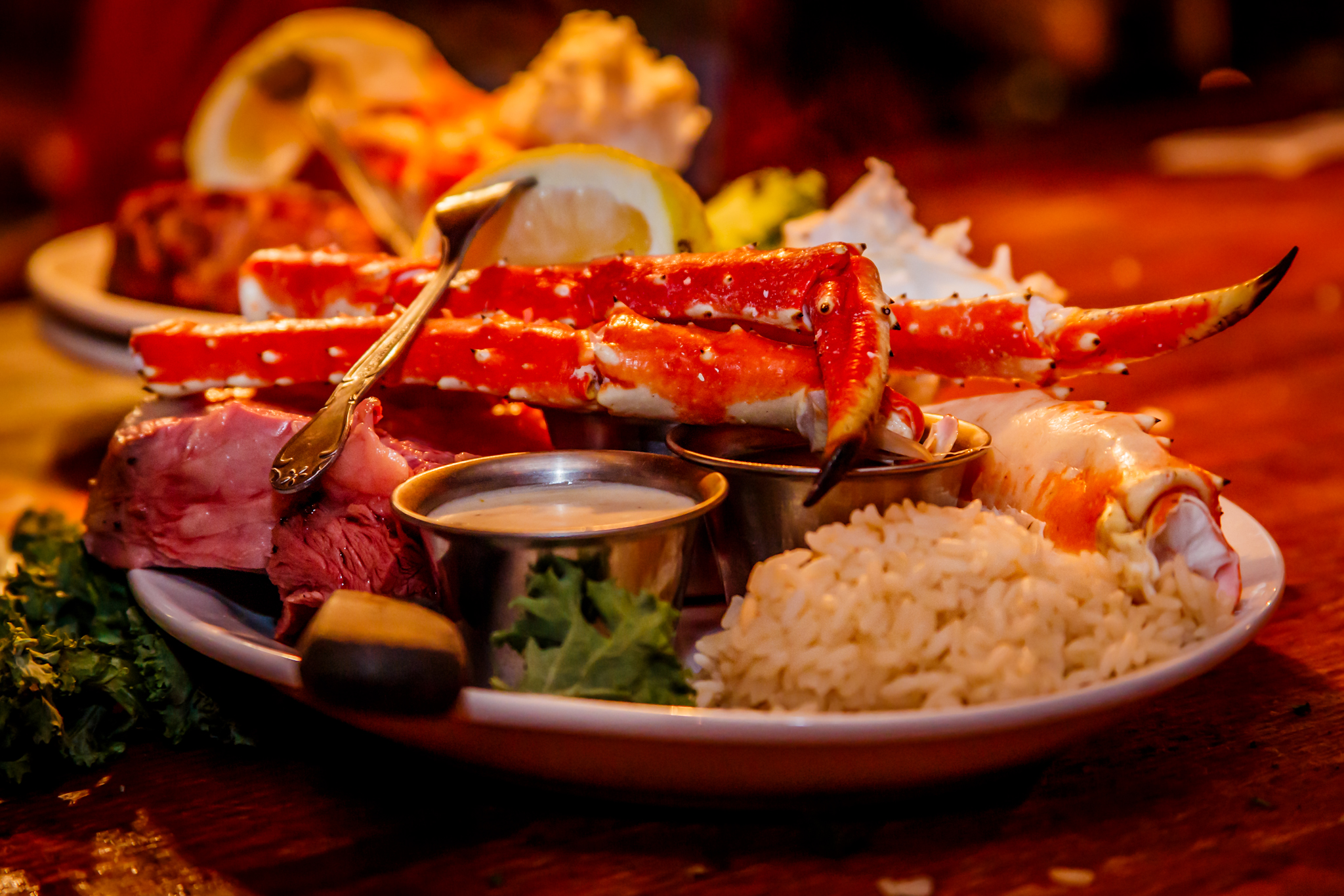 plate with steak and crab claws and sauce and rice