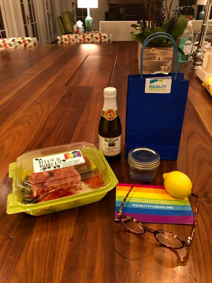 A Happy Hour to-go package, champagne, sliced meat & cheese, a lemon and a pair of eyeglasses.