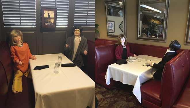Inflatable dolls seated in restaurant booth