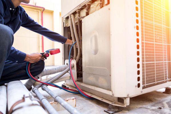 Image of repairman working on HVAC system